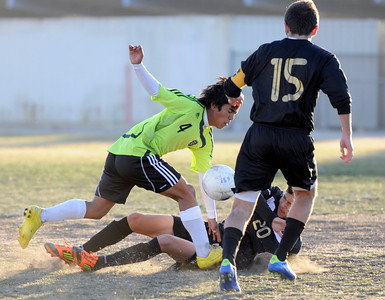 Palmdale#4 Nelson Rivera runs over Knight#20 Jorge Reynaga and past Knight#15 Alonso Medina in the first half of play. Knight defeated Palmdale 3-2 in a Golden League boys' soccer match. Palmdale, CA 2/1/2012(John McCoy/Staff Photographer)