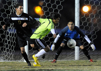 Knight#17 Miguel Ramirez and Knight#25 Hector Leon get in front of Palmdale#4 Nelson Rivera. Knight defeated Palmdale 3-2 in a Golden League boys' soccer match. Palmdale, CA 2/1/2012(John McCoy/Staff Photographer)