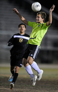 Palmdale#2 Steve Ramirez heads the ball away from Knight#13 Jessie Reyes. Knight defeated Palmdale 3-2 in a Golden League boys' soccer match. Palmdale, CA 2/1/2012(John McCoy/Staff Photographer)