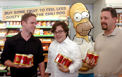 Left to right are Tuck Ross, 27, of Simi VAlley, Michael Becker, 28, of Burbank and Dave Ferguson, 35, of Santa Clarita, wait in line with their Buzz Cola at a 7-Eleven which has been changed into a Kwik-e-Mart for the upcoming, Simpson's movie.  (Tina Burch/Staff Photographer)