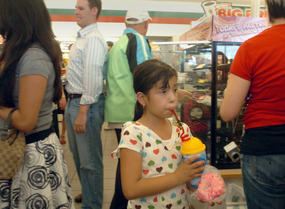 Yareth Hernandez, 8, drinks her Squishee and holds her donut with pink frosting and sprinkles, at the 7-Eleven in Burbank, Ca., on Monday, July 2, 2007, which was turned into a Kwik-e-Mart for the new Simson's movie.  (Tina Burch/Staff Photographer)