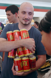 Peter Shaulis of North Hollywood, holds four 6-packs of Buzz Cola at the 7-Eleven in Burbank, Ca., which was changed into a Kwik-e-Mart for the upcoming Simpson's movie.  (Tina Burch/Staff Photographer)