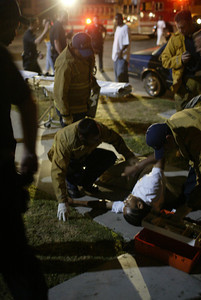 (7-24-04 South Los Angeles)  Los Angeles City Firefighters/PAramedics treat a Rollin 40's NHC gang member for a gunshot wound on 52nd and 6th in South Los Angeles. A male and female were shot while attending a wake with in the heavily gang populated area.(Hans Gutknecht/LA Daily News)