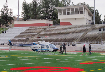 An LAPD helicopter crew team walk away from their helicopter at 2:15 p.m. Monday, Dec. 12, 2011 after he landed the craft on the Los Angeles Pierce College football field in Woodland Hills. An LAPD police cruiser responding to the scene got stuck in the mud in today's stormy weather. The crew, responding to the aircrafts warning system, landed the craft on the field as a precaution. (Dean Musgrove/Daily News Staff Photographer)