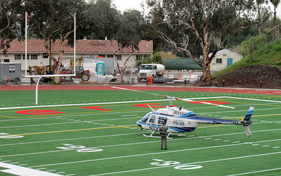 An LAPD helicopter crew member stands near his helicopter at 2:15 p.m. Monday, Dec. 12, 2011 after he landed the craft on the Los Angeles Pierce College football field in Woodland Hills. An LAPD police cruiser responding to the scene got stuck in the mud in today's stormy weather. The crew, responding to the aircrafts warning system, landed the craft on the field as a precaution. (Dean Musgrove/Daily News Staff Photographer)