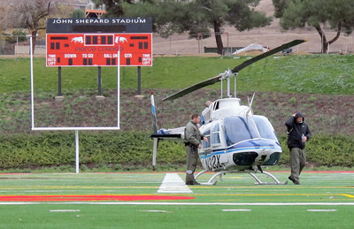 LAPD helicopter crew members secure their helicopter at 2:15 p.m. Monday, Dec. 12, 2011 after he landed the craft on the Los Angeles Pierce College football field in Woodland Hills. An LAPD police cruiser responding to the scene got stuck in the mud in today's stormy weather. The crew, responding to the aircrafts warning system, landed the craft on the field as a precaution. (Dean Musgrove/Daily News Staff Photographer)