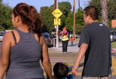 Crossing Guard Esther Munguia escorts a family across Winnetka Ave. Monday morning.  As part of the Start of School Strategic Plan-2011 scheduled for LAPD's Valley Traffic Division during the 2011/2012 school year, Valley Traffic Division conducted a Crossing Guard and Pedestrian Safety Enforcement Operation and Press Conference at Winnetka Avenue Elementary School.  This operation was conducted in an effort to promote crossing guard safety, and to improve pedestrian safety. While the crossing guard ensures the safety of the school children, traffic enforcement officers will ensure motorist yield the right of way to the crossing guard and students alike. The message is simple, yield the right away to a crossing guard who is protecting our children or be cited.  (Dean Musgrove/Staff Photographer)