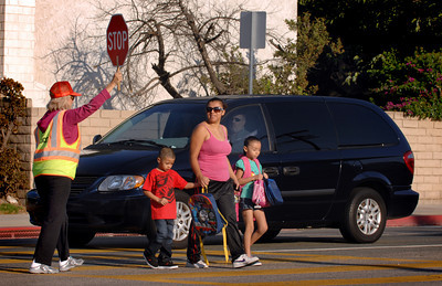 Crossing Guard Esther Munguia escorts Esmeralda Cortez and her children Carlos and Yulissa across Winnetka Ave. Monday morning.  As part of the Start of School Strategic Plan-2011 scheduled for LAPD's Valley Traffic Division during the 2011/2012 school year, Valley Traffic Division conducted a Crossing Guard and Pedestrian Safety Enforcement Operation and Press Conference at Winnetka Avenue Elementary School.  This operation was conducted in an effort to promote crossing guard safety, and to improve pedestrian safety. While the crossing guard ensures the safety of the school children, traffic enforcement officers will ensure motorist yield the right of way to the crossing guard and students alike. The message is simple, yield the right away to a crossing guard who is protecting our children or be cited.  (Dean Musgrove/Staff Photographer)