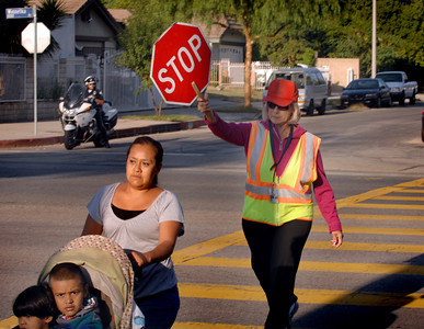 Crossing Guard Esther Munguia escorts a family across Winnetka Ave. Monday morning as a LAPD Valley Traffic Officer keeps a watchful eye.  As part of the Start of School Strategic Plan-2011 scheduled for LAPD's Valley Traffic Division during the 2011/2012 school year, Valley Traffic Division conducted a Crossing Guard and Pedestrian Safety Enforcement Operation and Press Conference at Winnetka Avenue Elementary School.  This operation was conducted in an effort to promote crossing guard safety, and to improve pedestrian safety. While the crossing guard ensures the safety of the school children, traffic enforcement officers will ensure motorist yield the right of way to the crossing guard and students alike. The message is simple, yield the right away to a crossing guard who is protecting our children or be cited.  (Dean Musgrove/Staff Photographer)
