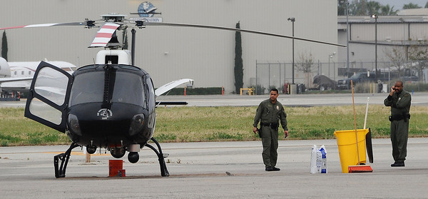 LAPD pilots look over their helicopter after they had to make a emergency landing at the Van Nuys airport early thing morning after it was shot at and started smoking. A suspect shot at the helicopter with a rifle from the area of Cohasset St. and Gloria Ave. None of the LAPD pilots were hurt and family members of the suspect were able to convince him to give up to police.  Van Nuys CA. April 24,2011.  Photo by Gene Blevins/LA Daily News