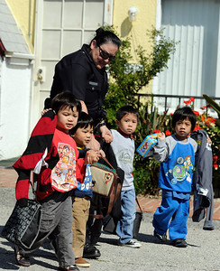LAPD officer Ruth Miramontes leads children from the Kidzhaven Child Care Center to their waiting parents. The center was near the site of an officer involved shooting in Sun Valley. (Hans Gutknecht/Staff Photographer)
