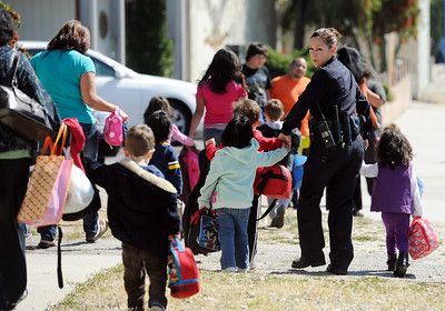 LAPD officer Sheila Gutierrez leads children from the Kidzhaven Child Care Center to their waiting parents. The center was near the site of an officer involved shooting in Sun Valley. (Hans Gutknecht/Staff Photographer)