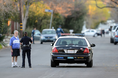 A Los Angeles Police officer talks to a resident on Manton Ave after a man shot a police officer was shot on Manton Ave near El Camino High School in Woodland Hills. (Hans Gutknecht/Staff Photographer)