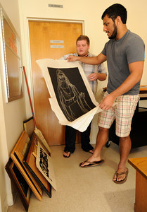(l-r) Jeff Creely and Kevin Kurian look through a stack of artwork that they picked out for purchase. Brand Library recently closed for major renovation, and has decided to thin out its archive of books and posters art work and recordings that have not been on display. The public was invited to purchase the surplus items as well as old desks, file cabinets and even furniture. Glendale, CA 4/7/2012(John McCoy/Staff Photographer)