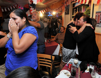 Members of the Chilean community who were gathered at Rincon Chileno Restaurant cheer, applaud and raise their glasses to toast the rescue of their countrymen while watching the action on television.  Hollywood, CA. 10-12-2010. (John McCoy/staff photographer)