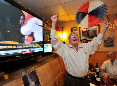 Pancho Cid stands up and cheers as the first miner is taken from the tube that carried him to the surface. Members of the Chilean community who were gathered at Rincon Chileno Restaurant cheer, applaud and raise their glasses to toast the rescue of their countrymen while watching the action on television.  Hollywood, CA. 10-12-2010. (John McCoy/staff photographer)