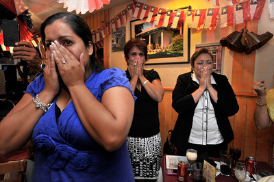 (l-r) Francesca Silva, Carmen Luz Carvajal, Angie Zetino hold back tears of joy. Members of the Chilean community who were gathered at Rincon Chileno Restaurant cheer, applaud and raise their glasses to toast the rescue of their countrymen while watching the action on television.  Hollywood, CA. 10-12-2010. (John McCoy/staff photographer)