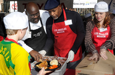 (l-r) David Thomas from the LA Mission helps celebrities James Pickens Jr. and Sarah Drew serve up a meal. The Los Angeles Mission held its annual Christmas event to feed and provide gifts to the less fortunate. Chef Ben Ford whipped up a holiday meal with the help of celebrities that included Gilles Marini, Sarah Drew and teen heartthrob BooBoo Stewart from the film Twilight-Breaking Dawn. After receiving a meal, Children were escorted to a tent where they had a visit with Santa and received gifts. Nearly 4000 people were expected to receive charity at the event.Los Angeles, CA 12/23/2011(John McCoy/Staff Photographer)