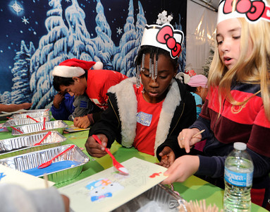 (l-r) Tamarson Butler,7, and Emily Grace Reaves,10, work on Christmas crafts. The Los Angeles Mission held its annual Christmas event to feed and provide gifts to the less fortunate. Chef Ben Ford whipped up a holiday meal with the help of celebrities that included Gilles Marini, Sarah Drew and teen heartthrob BooBoo Stewart from the film Twilight-Breaking Dawn. After receiving a meal, Children were escorted to a tent where they had a visit with Santa and received gifts. Nearly 4000 people were expected to receive charity at the event.Los Angeles, CA 12/23/2011(John McCoy/Staff Photographer)