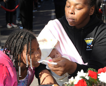 (l-r) Tamercion Butler and her baby sister Lynina get help eating from their Mom Tulina Millner. The Los Angeles Mission held its annual Christmas event to feed and provide gifts to the less fortunate. Chef Ben Ford whipped up a holiday meal with the help of celebrities that included Gilles Marini, Sarah Drew and teen heartthrob BooBoo Stewart from the film Twilight-Breaking Dawn. After receiving a meal, Children were escorted to a tent where they had a visit with Santa and received gifts. Nearly 4000 people were expected to receive charity at the event.Los Angeles, CA 12/23/2011(John McCoy/Staff Photographer)