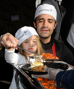 Actor Gilles Marini and his daughter Guliana,5, serve up some carrots. The Los Angeles Mission held its annual Christmas event to feed and provide gifts to the less fortunate. Chef Ben Ford whipped up a holiday meal with the help of celebrities that included Gilles Marini, Sarah Drew and teen heartthrob BooBoo Stewart from the film Twilight-Breaking Dawn. After receiving a meal, Children were escorted to a tent where they had a visit with Santa and received gifts. Nearly 4000 people were expected to receive charity at the event.Los Angeles, CA 12/23/2011(John McCoy/Staff Photographer)