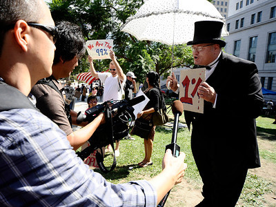 Eric Headman dresses up as the Mr. Monopoly game character and joins the several dozen protesters who blame the economic meltdown on greedy corporations who set up tents over the weekend on sidewalks by Los Angeles City Hall. No arrests have been made, and police say the demonstrators can stay unless they cause problems. The protester LA have gathered in support and  sympathy for the 700 Wall Street protesters who were arrested in New York over the weekend. Los Angeles CA.  Oct 3,2011. Photo by Gene Blevins/LA Daily News