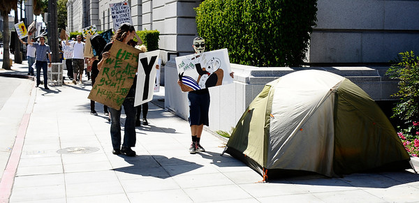 Several dozen protesters march around Los Angeles city hall who blame the economic meltdown on greedy corporations, set up tents over the weekend on sidewalks by Los Angeles City Hall. No arrests have been made, and police say the demonstrators can stay unless they cause problems. The protester LA have gathered in support and  sympathy for the 700 Wall Street protesters who were arrested in New York over the weekend. Los Angeles CA.  Oct 3,2011. Photo by Gene Blevins/LA Daily News