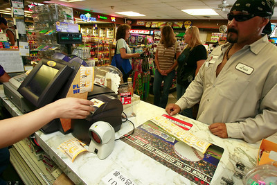 Luis Salazar of Northridge purchases $96 in Mega Millions Lotto tickets for himself and his co-workers for Friday night's drawing worth $330 Million from  Evaristo Fluerta (not shown), left, at Valencia Liquor in Newhall, CA, on Friday, Aug. 31, 2007 which has already produced a few large winners and one over $34 million. As Salazar waits for his final ticket to print, Heather DeLeon, to his right, waits to purchase 220 tickets for her co-workers also. (John Lazar/L.A. Daily News Staff Photographer)