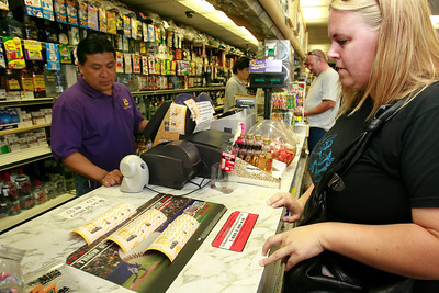 Heather DeLeon, right, waits for clerk Evaristo Fluerta to print a total of 44 tickets from a $220 pot she collected from her co-workers at Marathon Truck Body as other customers line up to purchase tickets for Friday night's Mega Millions Lotto tickets worth $330 Million at Valencia Liquor in Newhall, CA, on Friday, Aug. 31, 2007 which has already produced a few large winners and one over $34 million.  (John Lazar/L.A. Daily News Staff Photographer)