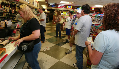 Heather DeLeon, left, waits for a total of 44 tickets to print for the $220 pot she collected from her co-workers at Marathon Truck Body as other customers line up to purchase tickets for Friday night's Mega Millions Lotto tickets worth $330 Million at Valencia Liquor in Newhall, CA, on Friday, Aug. 31, 2007 which has already produced a few large winners and one over $34 million.  (John Lazar/L.A. Daily News Staff Photographer)