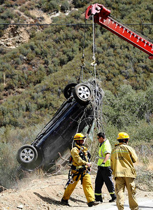 Los Angeles County fire search and rescue work on bringing up from over the edge were David Lavau, whose car had plunged 200 feet off a remote mountain road, was found on Thursday, Sept. 29, 2011 by his family members, who had enlisted the help of a missing persons detective. Lavau suffered multiple rib fractures, a broken arm and multiple fractures in his back. While he was being rescued, another vehicle was found nearby, its driver dead. Authorities don't know if that vehicle was involved in a collision with Lavau's car, or if it was a separate accident. CASTAIC CA  Sept 30,2011. Photo by Gene Blevins/LA Daily News