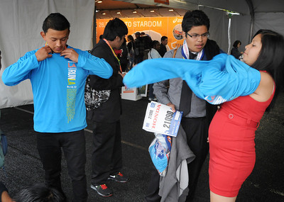 Students from Camino Nuevo High School, Angel Lopez, Daniel Santana and Brenda Baresi try on t-shirts that were given to them after they received their bibs. Participants in the Los Angeles Marathon arrived at 10AM Friday morning at Dodger Stadium to get their bib numbers, and check out a variety of sponsor tents where running merchandise was being sold. Los Angeles, CA 3/16/2012(John McCoy/Staff Photographer)