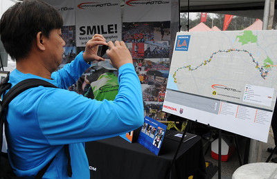 George Agagas, froom Huntington Beach, takes a photo of the race course map. Participants in the Los Angeles Marathon arrived at 10AM Friday morning at Dodger Stadium to get their bib numbers, and check out a variety of sponsor tents where running merchandise was being sold. Los Angeles, CA 3/16/2012(John McCoy/Staff Photographer)