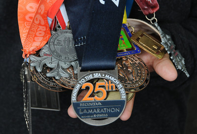 Javier Martinez, a student from Camino Nuevo High School, wears medals he received from running in long distance events. Participants in the Los Angeles Marathon arrived at 10AM Friday morning at Dodger Stadium to get their bib numbers, and check out a variety of sponsor tents where running merchandise was being sold. Los Angeles, CA 3/16/2012(John McCoy/Staff Photographer)