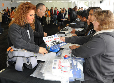 Irma Garcia traveled from Mexico to run in the marathon. Here Garcia gets her bib from volunteer Lori Davison. Participants in the Los Angeles Marathon arrived at 10AM Friday morning at Dodger Stadium to get their bib numbers, and check out a variety of sponsor tents where running merchandise was being sold. Los Angeles, CA 3/16/2012(John McCoy/Staff Photographer)
