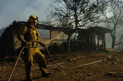 A firefighter stands in front of a burned out home on Carbon Canyon road on Monday morning in Malibu.  The only house that has burned on Monday.  (Tina Burch/Staff Photographer)