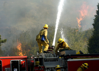 In Malibu, Ca., on the corner of Carbon Canyon Road and PCH, firefighters work on a fire next to Fire Station #70 on Monday morning, Oct. 22, 2007.  (Tina Burch/STaff Photograper)
