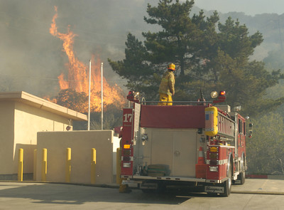 At Fire Station #70 at the corner of PCH and Carbon Canyon Road a fire comes up to the station while a firefighter prepares to stop it in Malibu, Ca. on Monday, Oct. 22, 2007.  (Tina Burch?Staff Photographer)