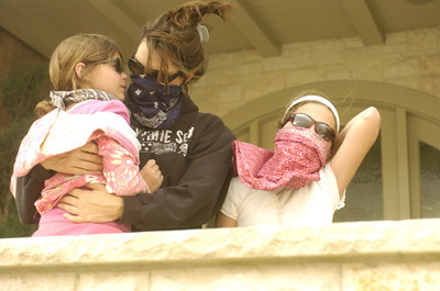 Cheryl CHadwick and her two daughters, Chelsea, 7, and Arielle, 10, watch the fire from their home on PCH at the corner of Carbon Canyon Road on Monday morning.  (Tina Burch/Staff Photographer)