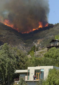 A fire heads down a canyon near Rambla Pacifico Road in Malibu, Ca., on Monday, Oct.22, 2007 while people hang out on their deck.  (Tina Burch/Staff Photographer)