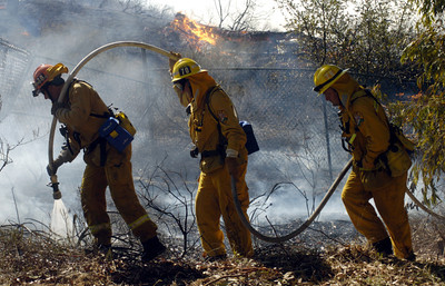 Firemen carry a hose to put out a fire along a hillside at Rambla Pacifico Road in Malibu, Ca., on MOnday, Oct. 22, 2007.  (Tina Burch/Staff Photographer)