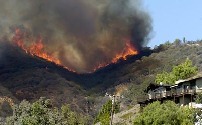 Fire heads down a canyon towards homes near Rambla Pacifico Road in Malibu, Ca., on Monday, Oct. 22, 2007.  (Tina Burch/Staff Photographer)