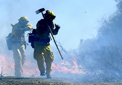 Firemen run from a fire which jumped the fireroad near Rambla Pacifico Road in Malibu, Ca., on Monday, Oct. 22, 2007.  (Tina Burch/Staff Photographer)