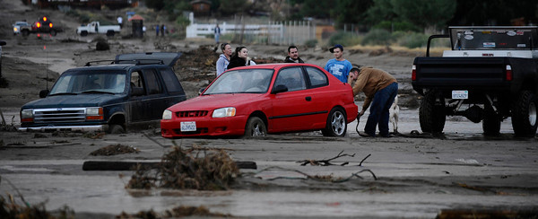 Residents of Lake Los Angeles try to dig their cars out of the mud after monsoon storms causing heavy flooding and also caused a water main to break in the area of Palmdale Blvd. and 170th east. Lake Los Angeles CA. Sept 10,2011.  Photo by Gene Blevins/LA DailyNews