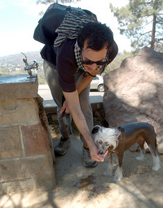 After hiking on the Mount Hollywood Hiking Trail in Griffith Park, Trinidad Garcia, 27, stops to give his Chinese Crested dog some water on Monday, August 27, 2007.  (Tina Burch/Staff Photographer)
