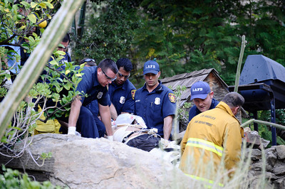 LA city firefighters take away murder suspect Stephen Clancy after he jump off a 50 foot cliff as LAPD SWAT officers moved in with taser guns when 7 plus hours of negotiations failed.  The suspect later died from his injuries at the hospital. West Hills CA.  June 5,2010..Photos by Gene Blevins/LA Daily News