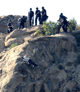 LAPD SWAT officers shoot taser guns at  murder suspect Stephen Clancy after 7 plus hours of negotiations failed. As SWAT officers shot their tasers Stephen Clancy decided to jump off the 50 foot  high cliff to the bottom were he died later from his injuries at the hospital. West Hills CA.  June 5,2010..Photos by Gene Blevins/LA Daily News