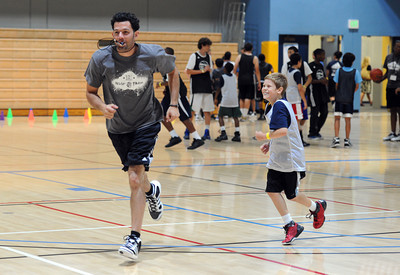 Former Los Angeles Laker and New Jersey Nets guard Jordan Farmar works with Parker Golub, 10-years-old, Hollywood, during his fourth annual Hoop Farm Basketball Camp at UCLAÕs John Wooden Center. (Hans Gutknecht/Staff Photographer)