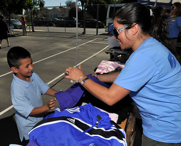 A Big-rig tractor and trailer showed up at Saticoy Elementary school Thursday to distribute school clothing to needy kids.  Operation School Bell, an outreach program from the Assistance League of Southern California, was on hand, along with volunteers from Universal Studios, to provide clothing for students from 32 schools in the San Fernando Valley. Each of the children received two white polo shirts, two navy blue bottoms (shorts, pants, shorts or jumper), a belt, five pairs of underwear, one pair of shoes, five pairs of socks, a jacket, a backpack, a grooming kit, and a book.  Universal Studio employees also provided a gift of clothing to the children to take home for a parent or sibling. North Hollywood, CA.11-4-2010. (John McCoy/staff photographer)
