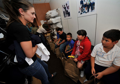 Stacey Kwiatkowski works with kids inside a Big-rig tractor and trailer showed up at Saticoy Elementary school Thursday to distribute school clothing to needy kids.  Operation School Bell, an outreach program from the Assistance League of Southern California, was on hand, along with volunteers from Universal Studios, to provide clothing for students from 32 schools in the San Fernando Valley. Each of the children received two white polo shirts, two navy blue bottoms (shorts, pants, shorts or jumper), a belt, five pairs of underwear, one pair of shoes, five pairs of socks, a jacket, a backpack, a grooming kit, and a book.  Universal Studio employees also provided a gift of clothing to the children to take home for a parent or sibling. North Hollywood, CA.11-4-2010. (John McCoy/staff photographer)